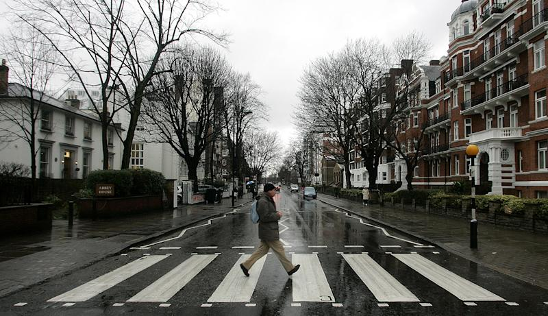 """FILE - In this file photo taken Feb. 16, 2010, a man walks on the zebra crossing made famous from the album cover of The Beatles' """"Abbey Road"""" in front of Abbey Road Studios, seen at left, in London. London counts at least 11 Abbey Roads, with potential tourist pitfalls in neighborhoods such as Barking or Bexleyheath, both of which are on the outer edges of central London. In the British capital, as elsewhere, the common street name harkens back to the medieval priories that once dotted the area. (AP Photo/Akira Suemori, File)"""