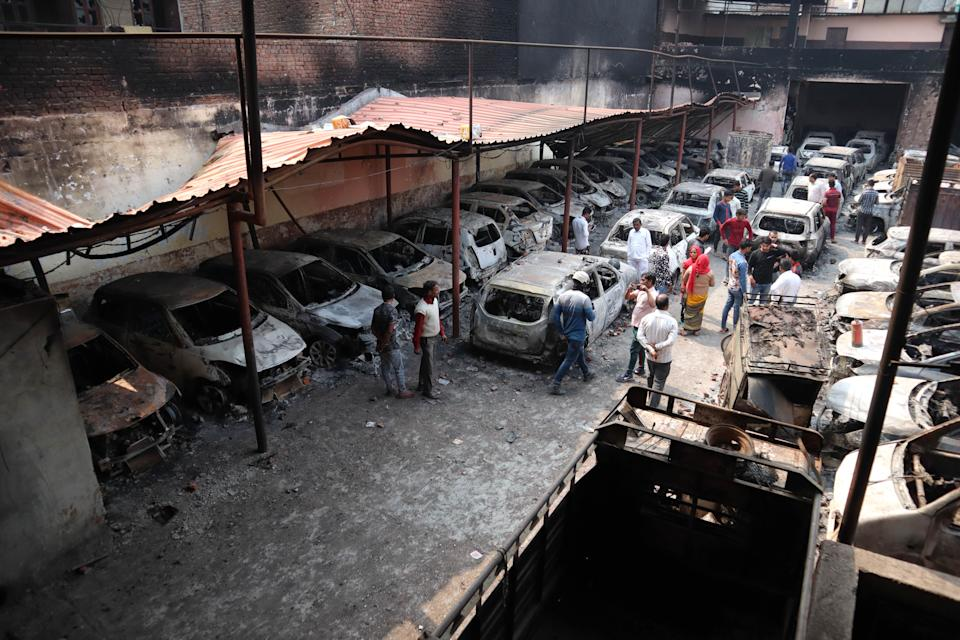 People walk besides burnt cars after a parking space was set on fire by a mob during riots in Chandbagh area of New Delhi on 29 February 2020. (Photo by Muzamil Mattoo/NurPhoto via Getty Images)