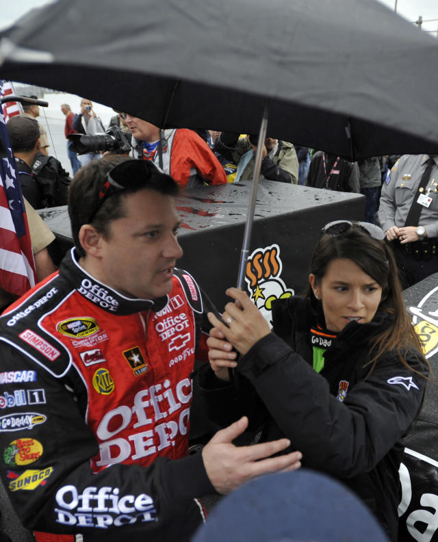 Danica Patrick, right, stands under an umbrella with Tony Stewart, left, during a rain delay in the start of the NASCAR Daytona 500 Sprint Cup series auto race in Daytona Beach, Fla., Sunday, Feb. 26, 2012. (AP Photo/Rainier Ehrhardt)