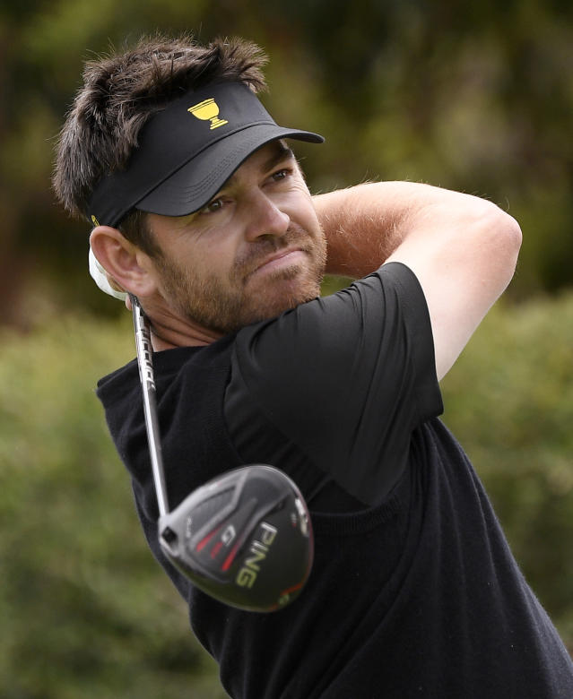 International team player Louis Oosthuizen of South Africa tees off at the 9th hole during their fourball match at the Royal Melbourne Golf Club in the opening rounds of the President's Cup golf tournament in Melbourne, Thursday, Dec. 12, 2019. (AP Photo/Andy Brownbill)