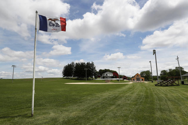 An Iowa flag waves in the wind over the field at the Field of Dreams movie site, Friday, June 5, 2020, in Dyersville, Iowa. Major League Baseball is building another field a few hundred yards down a corn-lined path from the famous movie site in eastern Iowa but unlike the original, it's unclear whether teams will show up for a game this time as the league and its players struggle to agree on plans for a coronavirus-shortened season. (AP Photo/Charlie Neibergall)
