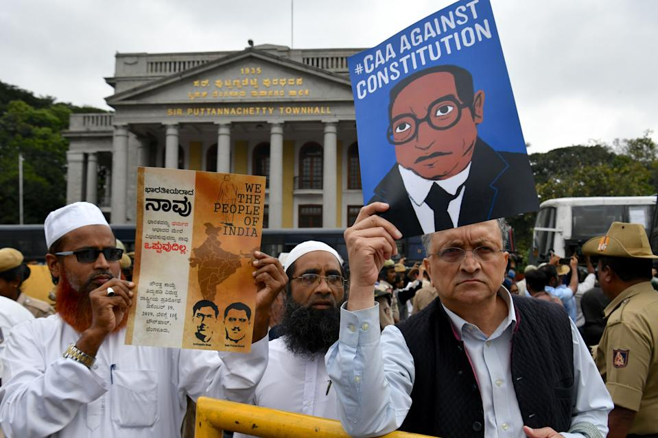 Historian Ramchandra Guha (R) holds a placard against India's new citizenship law during protest held in spite of a curfew in Bangalore on December 19, 2019. - Indians defied bans on assembly on December 19 in cities nationwide as anger swells against a citizenship law seen as discriminatory against Muslims, following days of protests, clashes and riots that have left six dead. (Photo by Manjunath Kiran / AFP) (Photo by MANJUNATH KIRAN/AFP via Getty Images)
