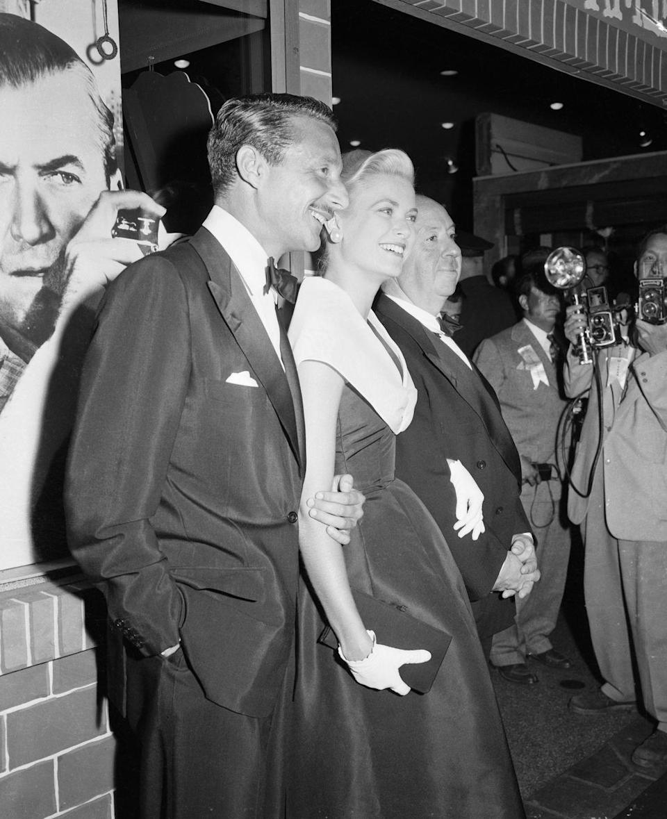 <p>Director Alfred Hitchcock, star Grace Kelly, and her boyfriend Oleg Cassini pose outside the theater during the 1954 premiere of<em> Rear Window. </em>The film was shot entirely on a soundstage, so the production crew created the largest indoor set at Paramount Studios of its time.</p>