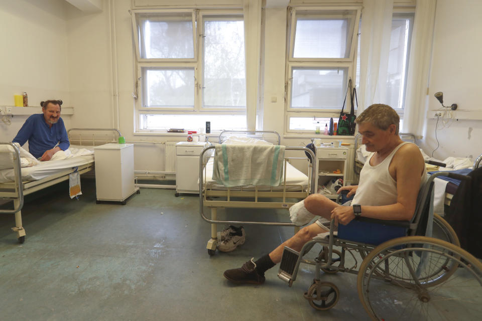 Patients sit in a ward of the hospital for the homeless in Budapest, Hungary, Thursday, April 14, 2021. A bitter conflict has emerged between Hungary's right-wing government and the liberal leadership of the country's capital city over a hospital for the homeless that may soon have to close. The Budapest hospital provides medical and social services and shelter to more than 1,000 people annually. But the Hungarian government has ordered it to vacate the state-owned building it occupies. Budapest's mayor says the eviction will risk the lives of the hospital's homeless patients as Hungary struggles with a deadly COVID-19 surge. (AP Photo/Laszlo Balogh)