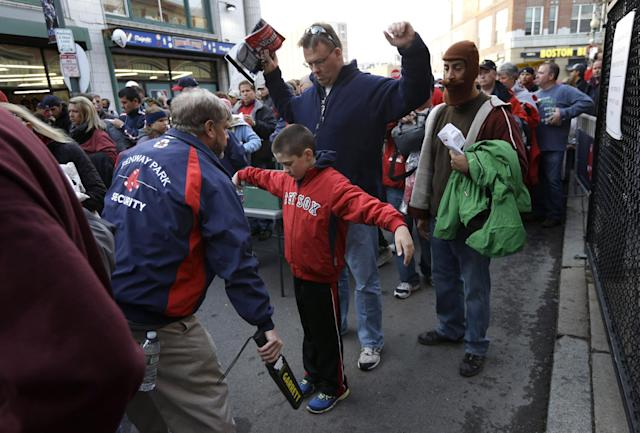 Jeffrey Corbett, top, and his son Joseph, 9, center, both of Arlington, Mass., raise their arms as they pass through security outside Fenway Park before Game 6 of baseball's World Series between the Boston Red Sox and St. Louis Cardinals Wednesday, Oct. 30, 2013, in Boston. (AP Photo/Steven Senne)