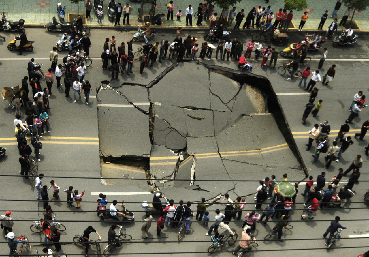 People look at a collapsed section of Shunwai Road in Nanchang, China's Jiangxi province, April 25, 2007. No one was injured in the accident and further investigations are underway, according to local media. Picture taken April 25, 2007. REUTERS/China Daily (CHINA) CHINA OUT - RTR1P1RN