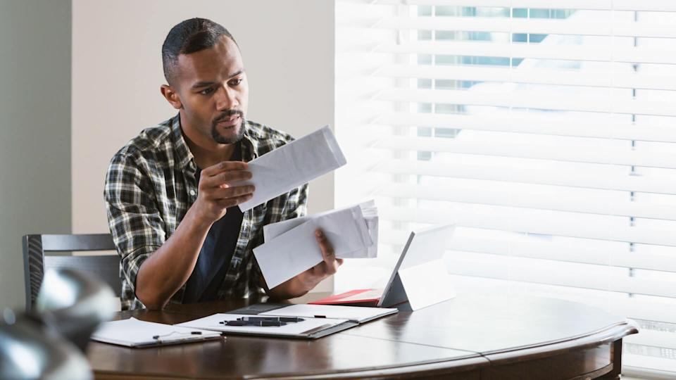 A young African-American man sitting at a desk by a window at home, paying bills.