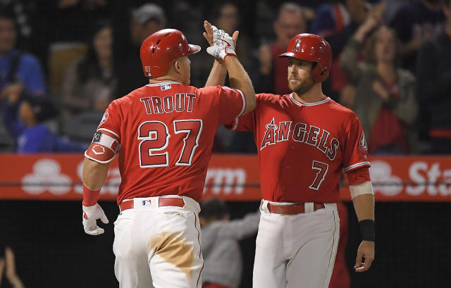 Los Angeles Angels' Mike Trout, left, is congratulated by Zack Cozart after hitting a two-run home run during the ninth inning of a baseball game against the Tampa Bay Rays on Saturday, May 19, 2018, in Anaheim, Calif. (AP Photo/Mark J. Terrill)