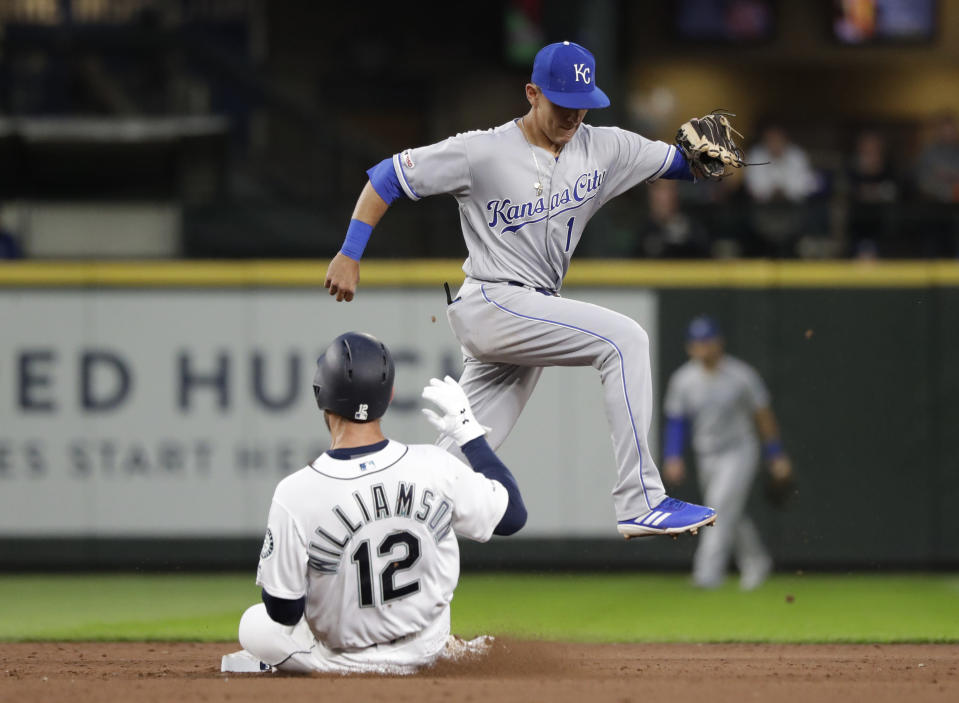 Kansas City Royals second baseman Nicky Lopez (1) leaps out of the way after forcing out Seattle Mariners' Mac Williamson (12) at second base to end the fifth inning of a baseball game Tuesday, June 18, 2019, in Seattle. (AP Photo/Elaine Thompson)