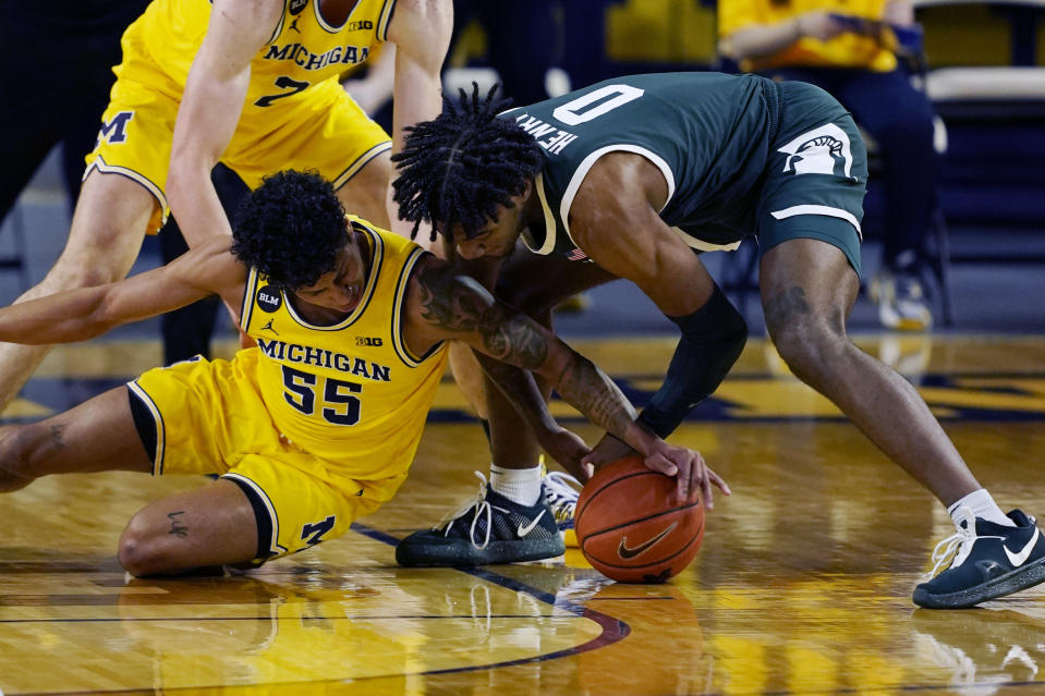 Michigan guard Eli Brooks (55) and Michigan State forward Aaron Henry (0) reach for the loose ball during the first half of an NCAA college basketball game, Thursday, March 4, 2021, in Ann Arbor, Mich. (AP Photo/Carlos Osorio)