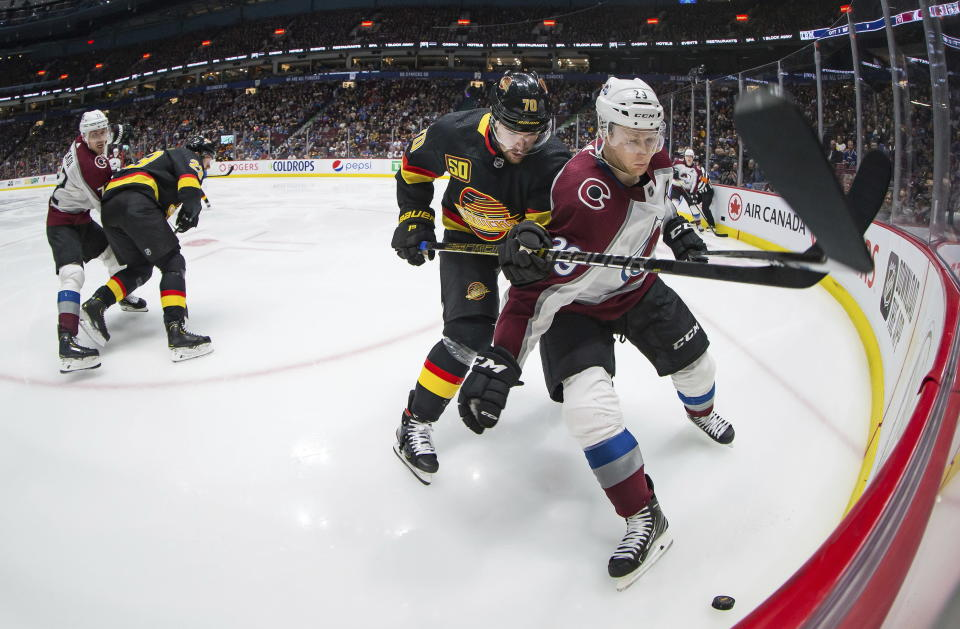 Vancouver Canucks' Tanner Pearson (70) checks Colorado Avalanche's Nathan MacKinnon (29) during the third period of an NHL hockey game Saturday, Nov. 16, 2019, in Vancouver, British Columbia. (Darryl Dyck/The Canadian Press via AP)