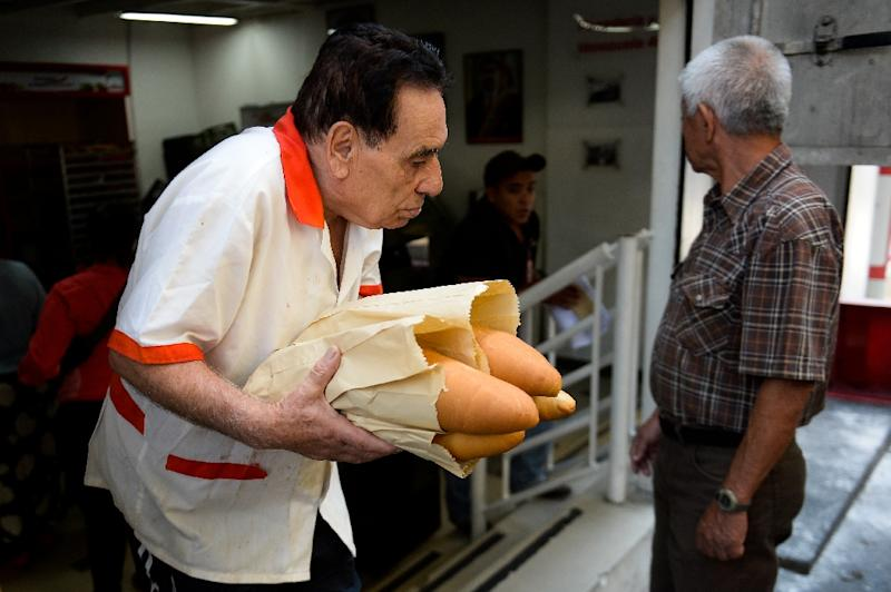 Customers line up for bread in the morning, at noon and in the evening (AFP Photo/Federico Parra)