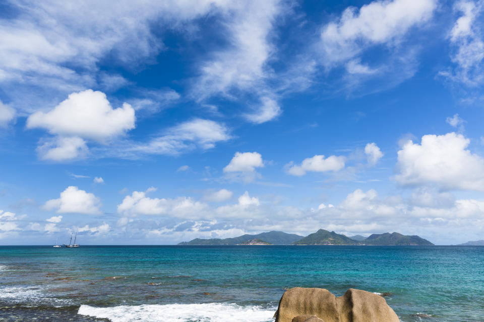 View at the wild north coast of La Digue, Seychelles with the island of Praslin in the background