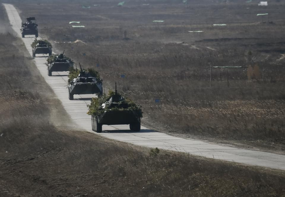 Ukrainian soldiers ride on military armoured personnel carriers as they take part in a military exercise near village of Goncharivske March 14, 2014. U.S. President Barack Obama said on Friday he still hopes for a diplomatic solution to the Ukraine crisis heading into a pivotal weekend. REUTERS/Gleb Garanich