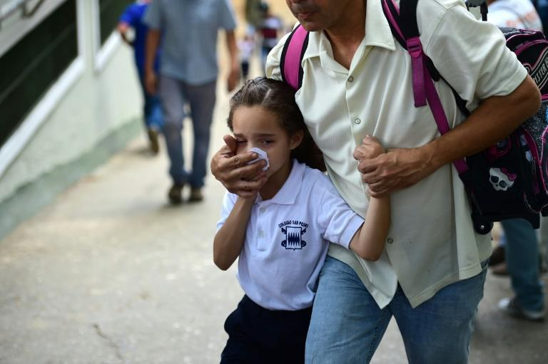 A schoolgirl covers her nose and mouth to avoid breathing tear gas shot by police at opponents of Venezuelan President Nicolas Maduro marching in Caracas on April 26, 2017