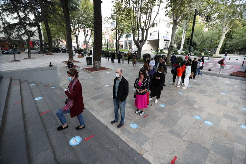 People line up outside a polling station during a parliamentary election in Tbilisi