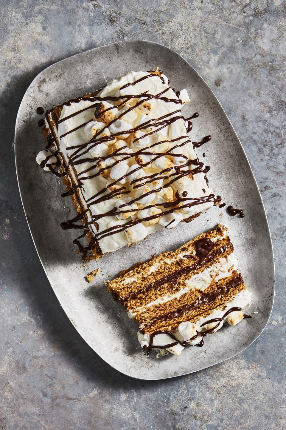 """<p>No lingering campfire smell here. Yep, you can whip up this cake without breaking out the fire pit or better yet, <a href=""""https://www.goodhousekeeping.com/food-recipes/dessert/g2497/no-cook-summer-desserts/"""" rel=""""nofollow noopener"""" target=""""_blank"""" data-ylk=""""slk:turning on the oven"""" class=""""link rapid-noclick-resp"""">turning on the oven</a>. </p><p><em><a href=""""https://www.goodhousekeeping.com/food-recipes/dessert/a45720/smores-icebox-cake-recipe/"""" rel=""""nofollow noopener"""" target=""""_blank"""" data-ylk=""""slk:Get the recipe for S'mores Icebox Cake »"""" class=""""link rapid-noclick-resp"""">Get the recipe for S'mores Icebox Cake »</a></em></p>"""