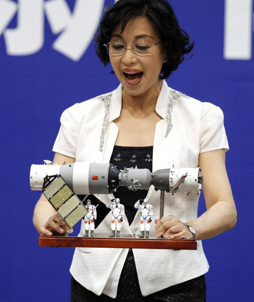 Wu ping, spokesperson for China's manned flight program, reacts as a solar panel drop from a scale model of the Shenzhou 9 module docking with China's Tiangong 1 space module and 3 astronauts during a press conference at the Jiuquan satellite launch center near Jiuquan in western China's Gansu province, Friday, June 15, 2012. China will launch three astronauts, including a mother of one who flies transport planes, to live and work on a space station for about a week, a major step in its goal of becoming only the third nation with a permanent base orbiting Earth. (AP Photo/Ng Han Guan)
