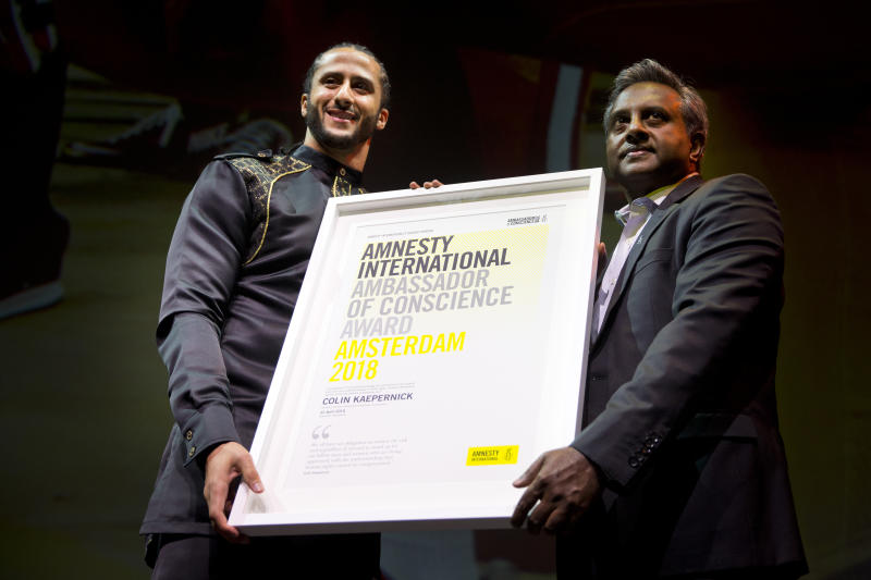 Former NFL quarterback and social justice activist Colin Kaepernick receives the Amnesty International Ambassador of Conscience Award for 2018 from Amnesty International Secretary General Salil Shetty, right, in Amsterdam, Saturday April 21, 2018. Kaepernick became a controversial figure when refusing to stand for the national anthem, instead he knelt to protest racial inequality and police brutality. (AP Photo/Peter Dejong)