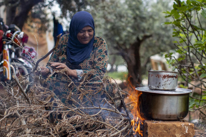 A Syrian refugee cooks food on a fire, at an informal refugee camp, in the town of Rihaniyye in the northern city of Tripoli, Lebanon, Thursday, April 8, 2021. For many Syrian refugee families in Lebanon, Ramadan comes as a hard life of displacement has gotten even harder after a pandemic year that deepened economic woes in their host country. (AP Photo/Hassan Ammar)
