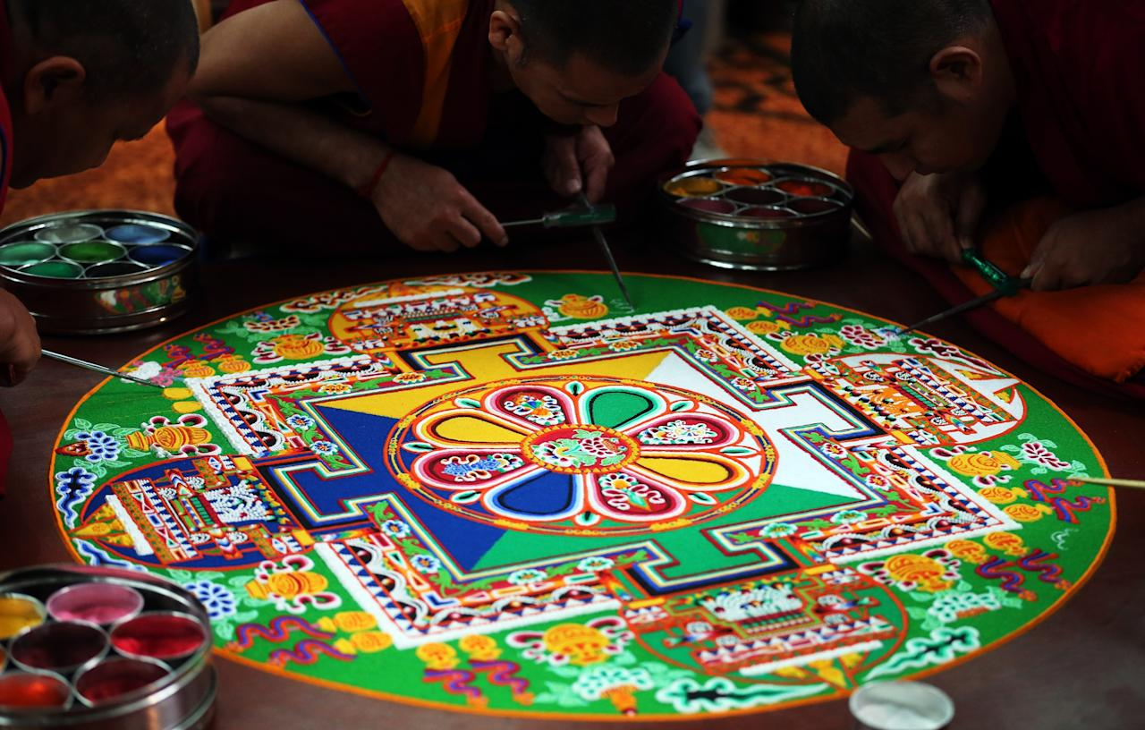 SALISBURY, ENGLAND - OCTOBER 03: Tibetan Monks from the Tashi Lhunpo Monastery, (L-R)Kachen Lobzang Tuskhor, Kachen Choedrak and Ven Lobzang Thokmed complete a Chenrezig Sand Mandala in Salisbury Cathedrals Chapter House on October 3, 2013 in Salisbury, England. The monks, who started the painstaking process of creating the sand mandela with millions of grains of coloured sand on Monday, will end it tomorrow in a destruction ceremony and procession to the River Avon. The monks who currently live in exile in India are visiting various places in the UK and Europe and will complete two more sand mandelas - which are an artistic tradition of Tibetan Buddhism and are a symbolic picture of the universe representing an imaginary palace - before returning home to their monastery in late November. (Photo by Matt Cardy/Getty Images)