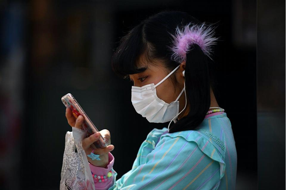 "<span class=""caption"">Getting kids to put down their phones doesn't have to be a battle.</span> <span class=""attribution""><a class=""link rapid-noclick-resp"" href=""https://www.gettyimages.com/detail/news-photo/girl-wearing-a-face-mask-checks-her-phone-as-she-waits-in-news-photo/1206683259"" rel=""nofollow noopener"" target=""_blank"" data-ylk=""slk:Carl Court/Getty Images"">Carl Court/Getty Images</a></span>"