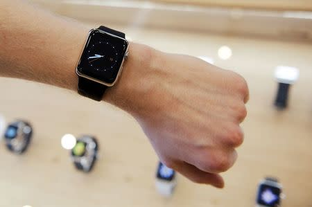 A salesman presents an Apple Watch to customers and journalists at an Apple Store in Berlin