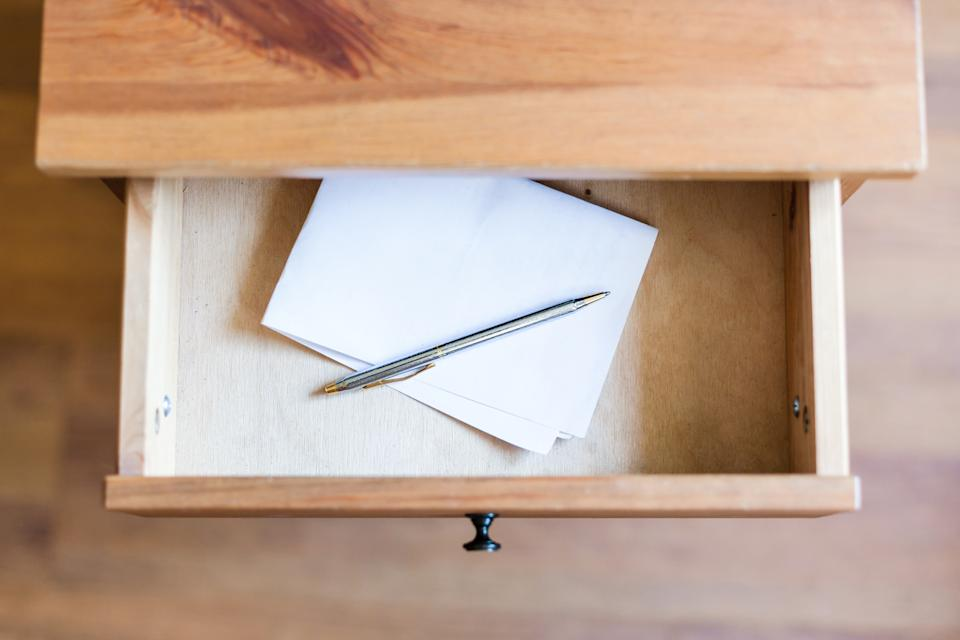 above view of folded sheet of paper and pen in open drawer of nightstand