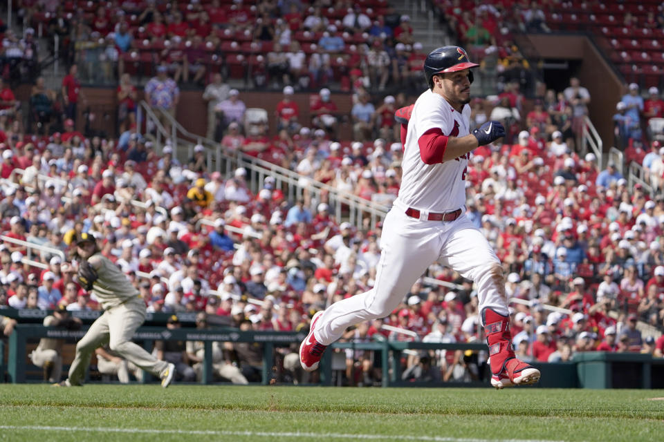 St. Louis Cardinals' Nolan Arenado runs to first for a single as San Diego Padres relief pitcher Pierce Johnson, left, fails to throw out Arenado at first during the fifth inning of a baseball game Sunday, Sept. 19, 2021, in St. Louis. (AP Photo/Jeff Roberson)