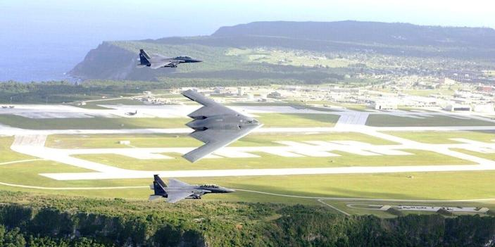 F-15E Strike Eagles and a B-2 Spirit bomber fly in formation over Andersen Air Force Base on Guam