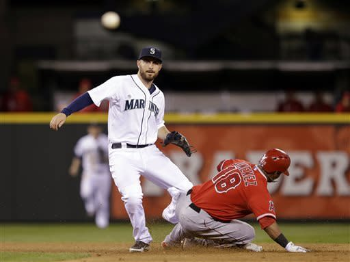 Seattle Mariners second baseman Dustin Ackley, left, watches his throw to first after forcing out Los Angeles Angels' Luis Jimenez at second base in the fifth inning of a baseball game Thursday, April 25, 2013, in Seattle. Ackley completed the double play. (AP Photo/Elaine Thompson)