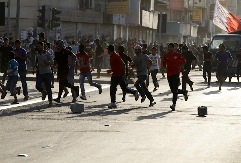 Bahraini anti-government protesters run as riot police open fire with tear gas and clashes begin in Sitra, Bahrain, on Wednesday, March 27, 2013. Clashes erupted after the politically charged funeral of Jaffar al-Taweel, 35, who relatives and rights activists say died from excessive tear gas inhalation. (AP Photo/Hasan Jamali)