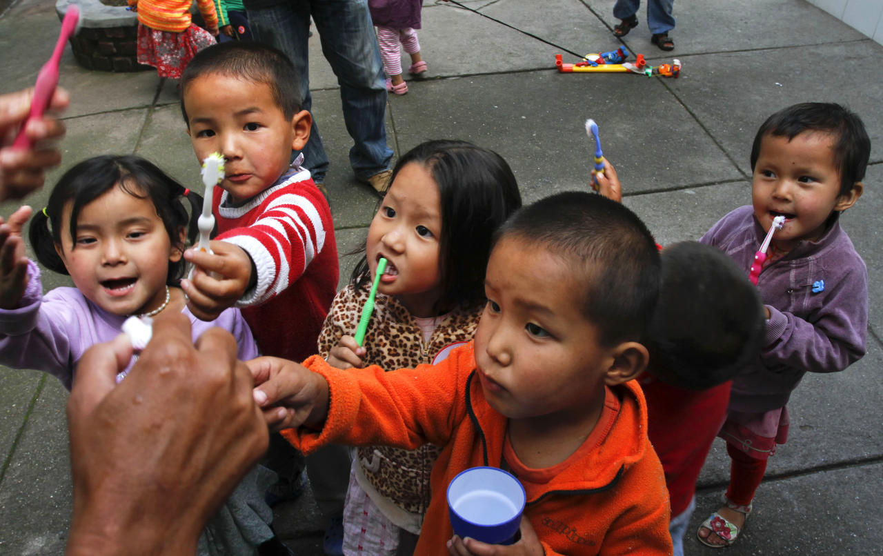 In this Sunday, June 19, 2011, photograph, Tibetan refugee children wait for toothpaste to be put on their toothbrushes after dinner at the Baby Home in the Tibetan Children's Village in Dharmsala, India. World Refugee Day is observed on Monday. In this Baby Home most children at the home are either orphans or have single working parents who are unable to care for them. More than 100,000 Tibetan refugees have made India their home and hundreds flee to India each year due to political and religious repression in Tibet under Chinese occupation. (AP Photo/Ashwini Bhatia)