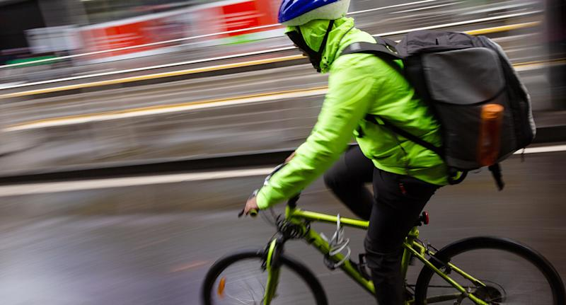 Photo shows a food delivery rider on a bicycle.