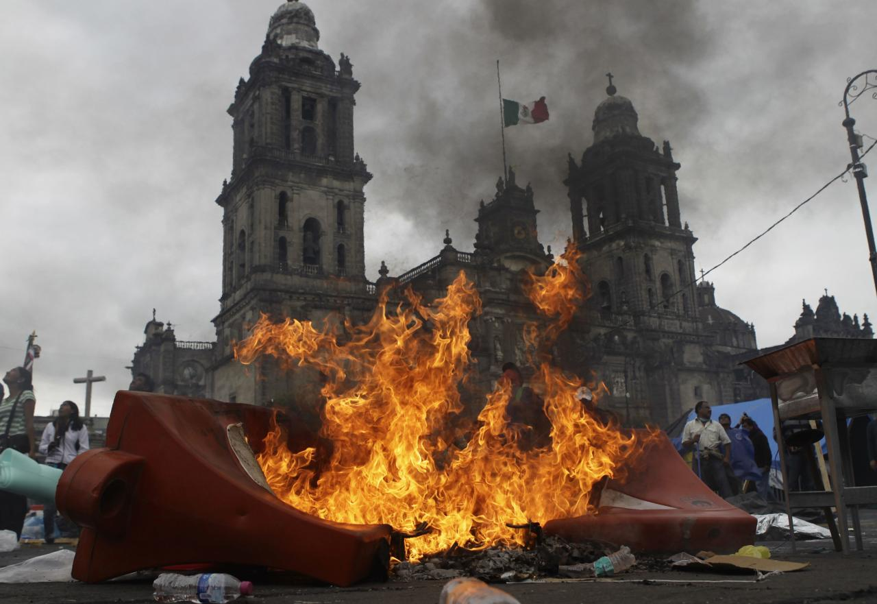 Members of the teachers' union CNTE and protesters stand near a burning barricade before they are evicted from Zocalo Square by the riot police in downtown Mexico City September 13, 2013. Violence broke out in the historic heart of Mexico City on Friday as scores of riot police forcibly evicted thousands of striking teachers occupying the capital's iconic Zocalo just days before Independence Day celebrations in the capital. Firing tear gas at angry protesters, riot police braced for violence as they swept into downtown Mexico City to re-take control of the Zocalo and its surrounding streets, the culmination of weeks of protests that had seen teachers set up a massive protest camp in the world's second largest square. The Metropolitan Cathedral is pictured in the background. REUTERS/Henry Romero (MEXICO - Tags: CIVIL UNREST POLITICS EDUCATION BUSINESS EMPLOYMENT TPX IMAGES OF THE DAY)