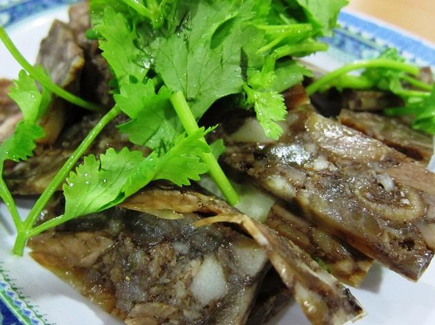 <b>Pig's Head Terrine (De Tao Chang)</b><br><br>Lee Kui (Ah Hoi) Restaurant <br>8-10 Mosque Street<br><br>Older generations of Teochews loathed to waste food so not even the pig's head is spared. They would chop it up, mix it with aromatic spices like star anise, cinnamon and cloves, and compact it with gelatin made from the pig's skin before chilling it. It is thinly sliced and is drier and tougher than the other cold Teochew dish, the pork knuckle aspic (Ter Ka Dang).<br><br>According to one of the owners of Ah Hoi, a Teochew family restaurant with a heritage of 44 years, the supply of pig's head is not as abundant as before, so pork meat is also added. <br><br>This terrine is usually served with a tangy garlic and chilli dip and can be eaten as a breakfast with porridge, or paired with beer or tea.