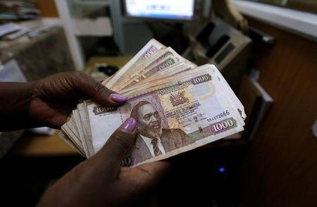 A teller counts Kenya shilling notes inside the cashier's booth at a forex exchange bureau in Kenya's capital Nairobi