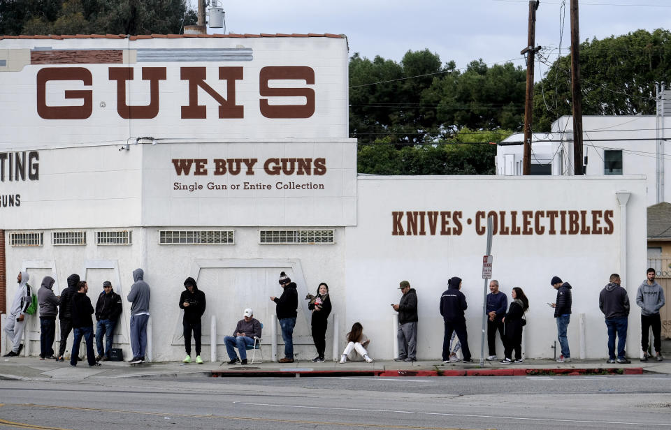 FILE - In this Sunday, March 15, 2020, file photo, people wait in line to enter a gun store in Culver City, Calif. After a year of pandemic lockdowns, mass shootings are back, but the guns never went away. As the U.S. inches toward a post-pandemic future, guns are arguably more present in the American psyche and more deeply embedded in American discourse than ever before. The past year's anxiety and loss fueled a rise in gun ownership across political and socio-economic lines. (AP Photo/Ringo H.W. Chiu, File)