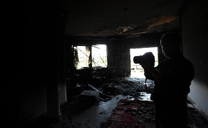 An American man takes photos of the burnt U.S. Consulate, after an attack that killed four Americans, including Ambassador Chris Stevens on the night of Tuesday, Sept. 11, 2012, in Benghazi, Libya, Thursday, Sept. 13, 2012. The American ambassador to Libya and three other Americans were killed when a mob of protesters and gunmen overwhelmed the U.S. Consulate in Benghazi, setting fire to it in outrage over a film that ridicules Islam's Prophet Muhammad. Ambassador Chris Stevens, 52, died as he and a group of embassy employees went to the consulate to try to evacuate staff as a crowd of hundreds attacked the consulate Tuesday evening, many of them firing machine-guns and rocket-propelled grenades. (AP photo/Mohammad Hannon)