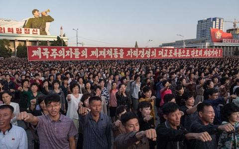Participants of a mass rally shout slogans as they gather before a banner reading 'let us beat down the sanctions of the imperialists with great progress of self-reliance' on Kim Il-Sung sqaure in Pyongyang on September 23, 2017 - Credit: AFP