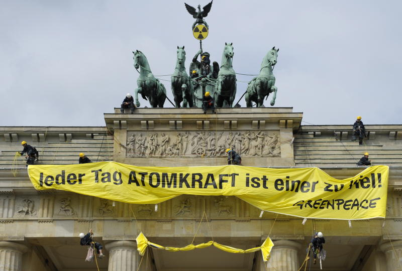 Greenpeace activists roll out a banner reading : ' Every day with nuclear power is one day too much' on top of the Brandenburg Gate with the Quadriga  in Berlin, Sunday May 29, 2011 to protests against the nuclear power policy of German Government.  (AP Photo/dapd/Michael Gottschalk)