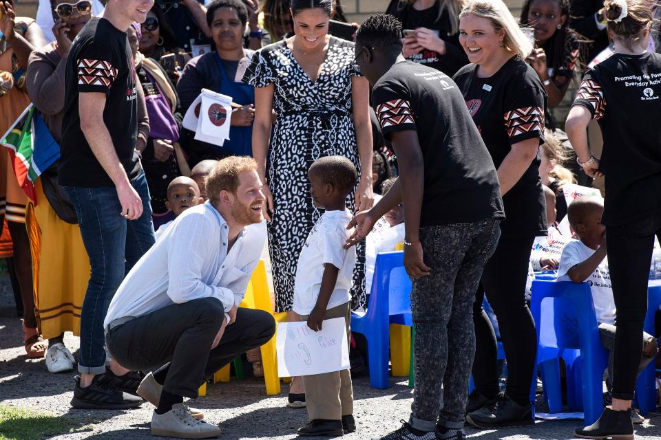 Prince Harry opted for a white linen shirt, grey chinos and grey trainers to visit the township of Nyanga in Cape Town [Photo: Getty Images]