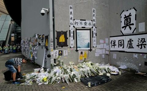 A woman cleans up a makeshift memorial near government headquarters in Hong Kong, Tuesday, July 2, 2019 - Credit: AP