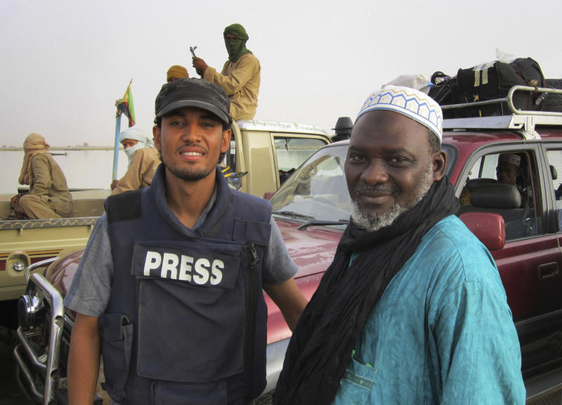 This photograph taken Friday May 18, 2012 shows AP reporter Baba Ahmed, left, with Elhadji Sidi Yattabar, of Mali's Islamic council, as they cross the Niger River some 16 kms (10 miles) from Timbuktu, Mali, escorted by fighters of the Ansar Dine. Ahmed made an emotional journey back to his hometown of Timbuktu where two months ago Tuareg rebels declared an independent state in the north amid a power vacuum created by the March 21 coup that ousted Mali's longtime leader.  (AP Photo)