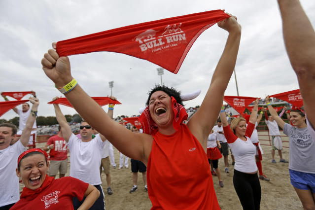Megan Wright, right, and Jennifer Campbell, left, both of Mobile, Ala., chant with the crowd before running alongside charging bulls during the Great Bull Run at the Georgia International Horse Park, Saturday, Oct. 19, 2013, in Conyers, Ga. The event, expected to attract 3,000 runners Saturday, is inspired by the annual running of the bulls in Pamplona, Spain and has future stops planned in Texas, Florida, California, Illinois and Pennsylvania. (AP Photo/David Goldman)