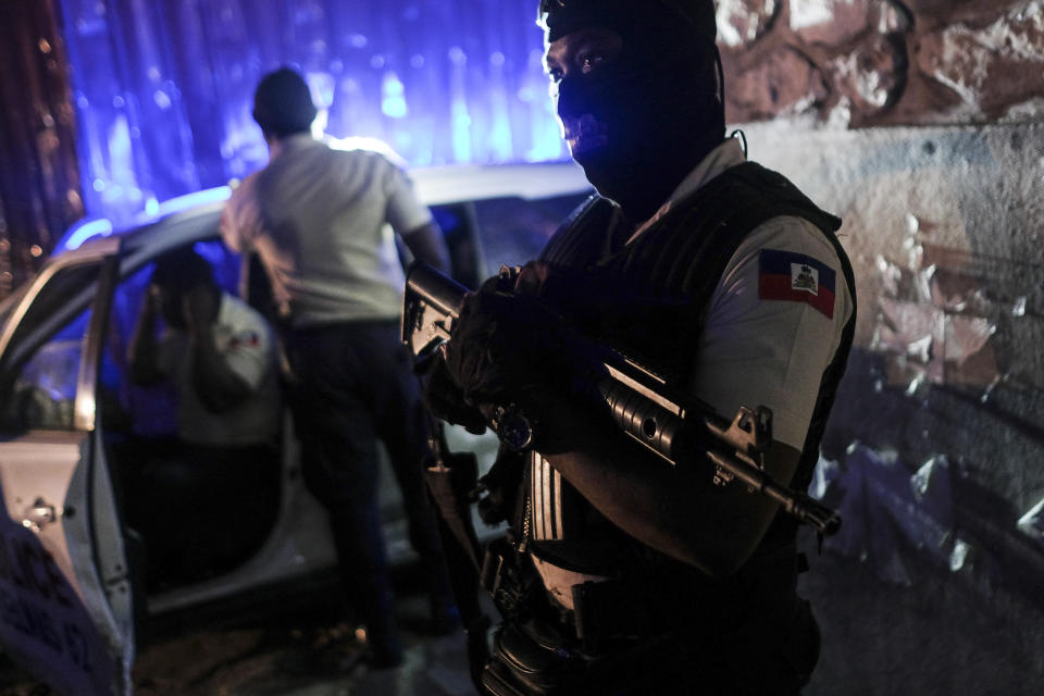 A police officer stands at an intersection in Port-au-Prince, Haiti, late Wednesday, July 14, 2021. Haiti is in the midst of a heightened security situation after the July 7 assassination of President Jovenel Moise. (AP Photo/Matias Delacroix)