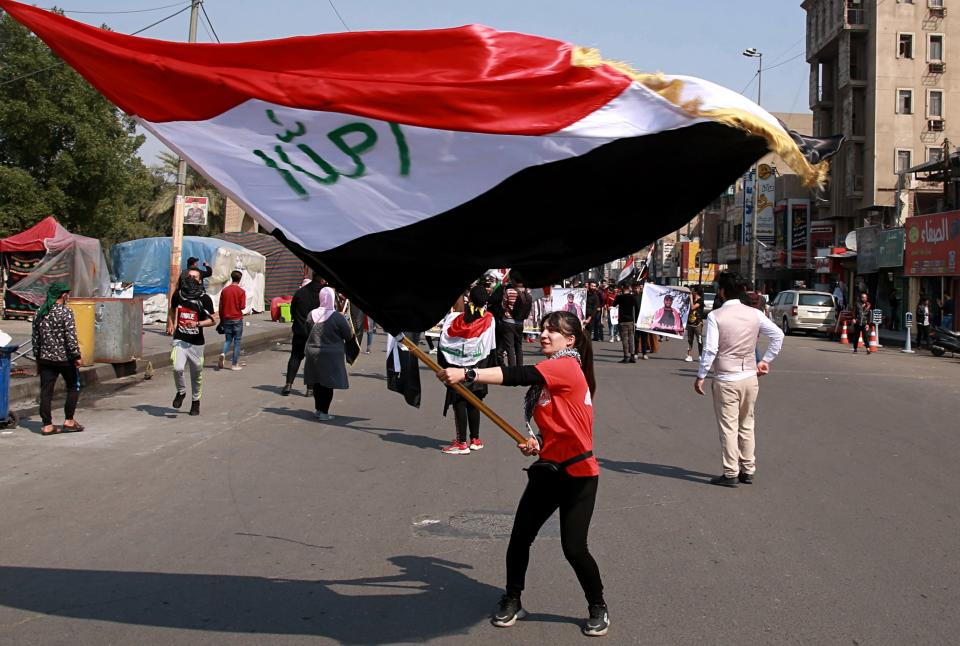 An anti-government protester waves an Iraqi flag during ongoing anti-government protests in Baghdad, Iraq, Sunday, Feb. 23, 2020. (AP Photo/Khalid Mohammed)