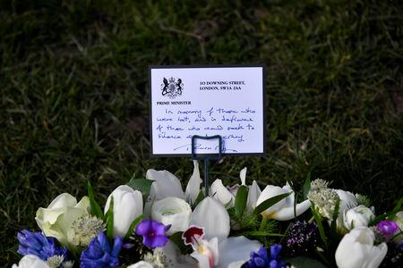FILE PHOTO: A hand-written message by Britain's Prime Minister Theresa May left with a wreath of flowers on Parliament Square in Westminster on the anniversary of the Westminster Bridge attack in London, Britain, March 22, 2018. REUTERS/Toby Melville/File Photo
