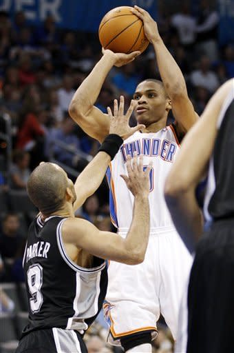 Oklahoma City Thunder guard Russell Westbrook, right, shoots over San Antonio Spurs guard Tony Parker (9), of France, in the third quarter of an NBA basketball game in Oklahoma City, Friday, March 16, 2012. (AP Photo/Sue Ogrocki)