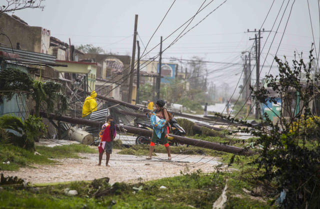 <p>Residents walk near downed power lines felled by Hurricane Irma, in Caibarien, Cuba, Saturday, Sept. 9, 2017. (Photo: Desmond Boylan/AP) </p>